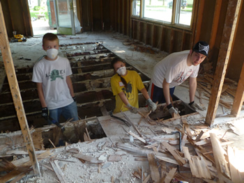 Haven King-Nobles, Teresa Jimenez Nickerson, and Scott Miller work to remove the flooring from a home slated for demolition.