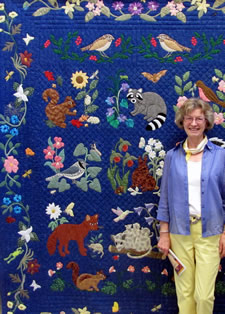 "Carolyn Stine with ""Woodland Creatures"" quilt, judged Best of Show"